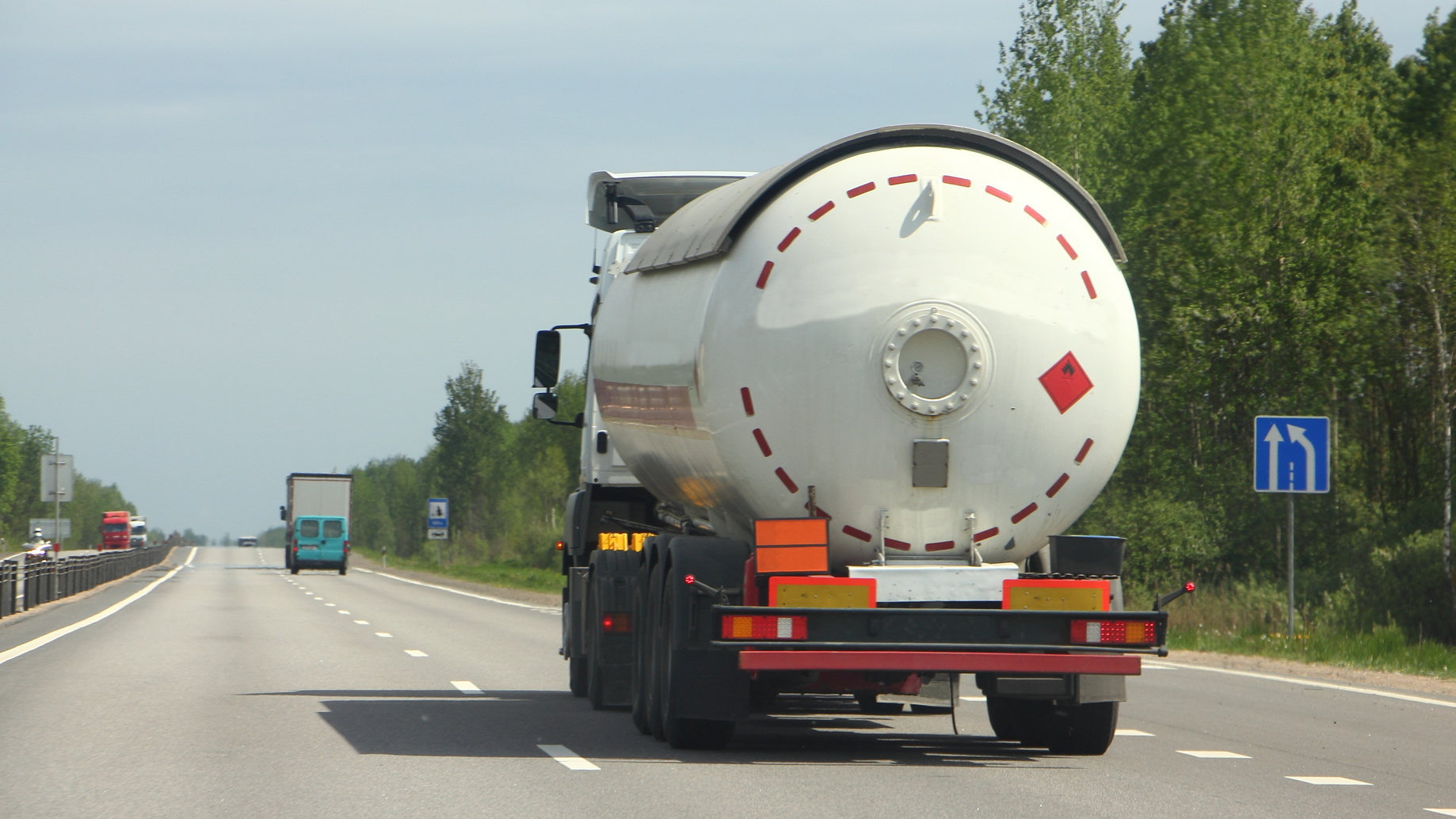 Semi truck with propane tank moving on asphalt road on a summer day - ADR dangerous cargo, side rear view